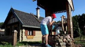 Equipe a água de derramamento de uma cubeta na garrafa na vila do russo filme