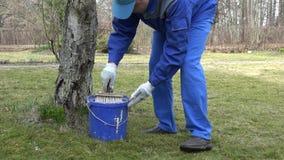 Equipe a árvore da pintura do trabalhador com a escova na mola adiantada no pomar 4K vídeos de arquivo