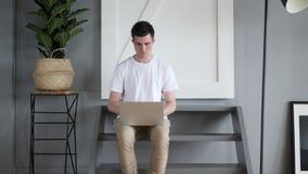 Equipe a abertura e a datilografia no portátil, sentando-se em escadas vídeos de arquivo