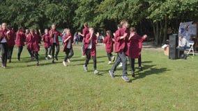 A equipe adolescente feliz dança em camisas idênticas fora no fundo de árvores verdes no evento filme