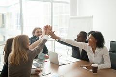 Equipe africana e caucasiano motivado entusiasmado do negócio que dá o hig foto de stock