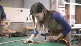 A equipe americana trabalha com couro real na mesa na sala da iluminação video estoque