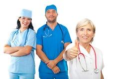 A equipe amigável dos doutores dá os polegares Fotografia de Stock Royalty Free