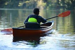 Equipe apenas em um lago bonito em um caiaque Fotos de Stock Royalty Free