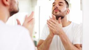 Equipe a aplicação após o óleo da barbeação à cara no banheiro vídeos de arquivo