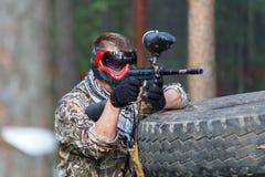 Equipe armado com o marcador do paintball atrás da fortificação do pneu Fotos de Stock