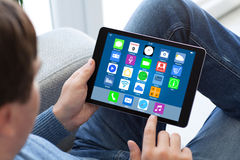 Equipe as calças de brim que guardam o tablet pc com apps dos ícones da tela home Fotos de Stock Royalty Free