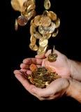 Equipe as mãos completamente do dinheiro que recebe uma chuva das moedas Fotos de Stock Royalty Free