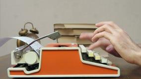 Equipe as mãos do ` s que datilografam em uma máquina de escrever retro vermelha em uma tabela com livros video estoque
