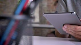 Equipe as mãos do ` s que guardam e que datilografam na tabuleta no escritório moderno filme