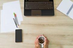Equipe as mãos do ` s que guardam o copo de café quente com smartphone, portátil, caderno, nota de papel e pena na tabela de made Imagem de Stock Royalty Free