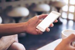 Equipe as mãos do ` s que guardam o telefone celular branco com tela vazia Foto de Stock Royalty Free