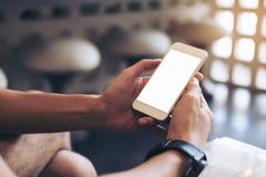 Equipe as mãos do ` s que guardam o telefone celular branco com tela vazia Fotografia de Stock