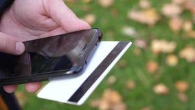 Equipe as mãos do ` s que guardam um cartão de crédito e que usam o telefone esperto para a compra em linha vídeos de arquivo
