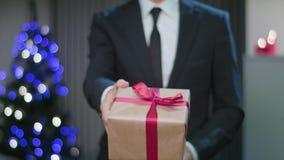 Equipe as mãos do ` s que guardam um presente do Natal filme