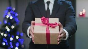 Equipe as mãos do ` s que guardam um presente do Natal vídeos de arquivo