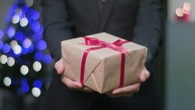 Equipe as mãos do ` s que guardam um presente do Natal video estoque