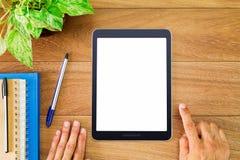 Equipe as mãos do ` s usando o tablet pc branco vazio da tela com originais, penas e potenciômetro da planta verde na tabela de m Fotografia de Stock Royalty Free