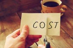 Equipe as mãos que cortam o cartão com o conceito do negócio do custo da palavra, cortando custos Fotografia de Stock Royalty Free