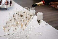 Equipe as mãos que derramam o champanhe de uma garrafa no vidro imagens de stock royalty free