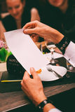 Equipe as mãos que guardam a folha de papel no café Imagens de Stock