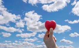 Equipe as mãos que guardam o coração vermelho até o céu azul Fotos de Stock