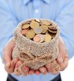 Equipe as mãos que guardaram o saco do dinheiro com euro- moedas Fotos de Stock