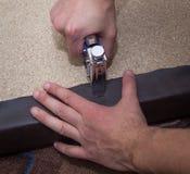 Equipe as mãos que prendem o couro à placa de partícula usando o grampeador fotos de stock