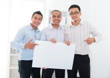 Equipe asiática do negócio que guardara uma bandeira vazia Imagem de Stock