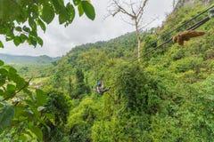 equipe atravessar na aventura do zipline a floresta no Lao imagem de stock royalty free