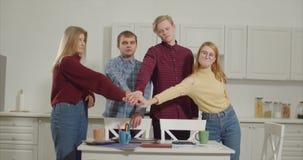 Equipe autônomo que faz a pilha das mãos no escritório domiciliário video estoque