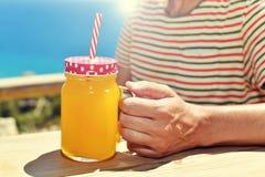 Equipe beber uma bebida alaranjada em um frasco de pedreiro Imagens de Stock Royalty Free