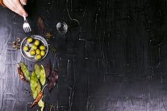 Equipe a bebida alcoólica das azeitonas das mordidas cercada por especiarias Fundo Textured escuro imagens de stock royalty free