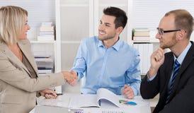 Equipe bem sucedida do negócio que senta-se em torno de uma tabela em uma reunião imagem de stock