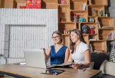 Equipe bem sucedida dos colegas inteligentes que conceituam junto usando o laptop moderno fotografia de stock