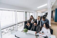 Equipe bem sucedida Grupo de executivos novos que trabalham e que comunicam-se junto no escrit?rio criativo imagens de stock royalty free