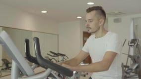 Equipe biking no gym, exercitando seus pés que fazem a cardio- bicicleta do ciclismo de treinamento vídeos de arquivo