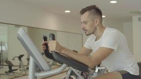 Equipe biking no gym, exercitando seus pés que fazem cardio- bicicletas do ciclismo de treinamento vídeos de arquivo