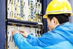 Equipe cabos de conexão da rede aos interruptores na sala de computador imagens de stock royalty free