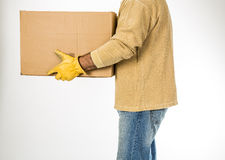 Equipe calças de brim vestindo e trabalhe as luvas que movem uma caixa Fotografia de Stock