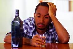 Equipe a camisa branca azul vestindo que senta-se pelo uísque guardando contrário da barra de vidro ao lado da garrafa do licor,  Imagens de Stock