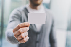 Equipe a camisa ocasional vestindo e mostrar o cartão branco vazio Fundo abstrato borrado modelo horizontal Imagem de Stock Royalty Free