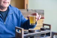 Equipe a cerveja da amostra de um voo no microbrewery local foto de stock