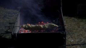 Equipe a colocação da carne crua em um assado quente para grelhar usando um par de tenazes de brasa de madeira, fim acima da vist Fotografia de Stock