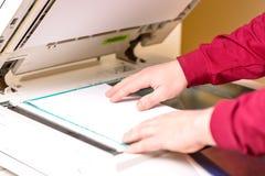 Equipe a colocação da folha de papel sobre a impressora para fazer a varredura Conceito do trabalho de escritório imagem de stock