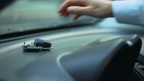 Equipe a colocação de chaves do carro sobre o painel, motorista que sae do automóvel estacionado aberto, roubo de carro vídeos de arquivo
