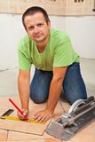Equipe a colocação de telhas de assoalho cerâmicas em uma construção nova Imagens de Stock Royalty Free