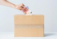 Equipe a colocação do euro- dinheiro na caixa da doação Fotografia de Stock