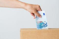 Equipe a colocação do euro- dinheiro na caixa da doação Fotos de Stock