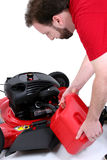 Equipe a colocação do gás na segadeira de gramado sobre o branco Imagens de Stock